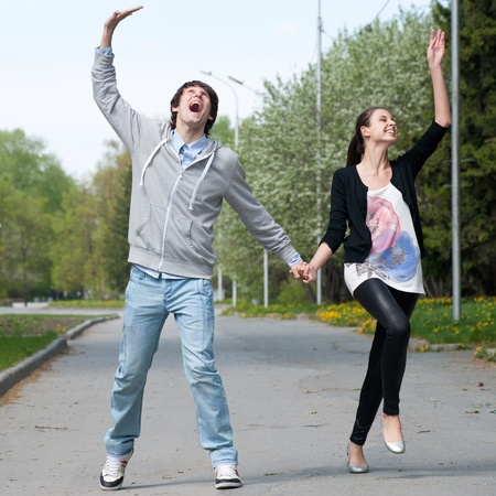 Happy young couple walking together in park and having fun photo
