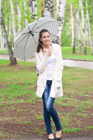 young woman: Young beautiful woman with umbrella walking in park Stock Photo