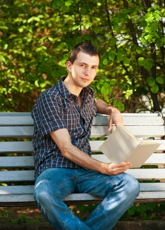 college boy: Handsome young man sitting on the bench and reading book outdoors