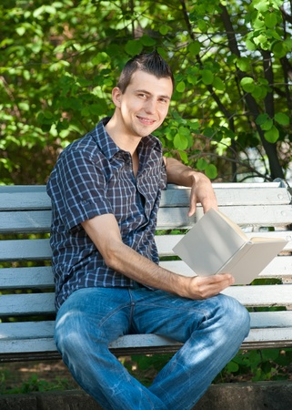 Handsome young man sitting on the bench and reading book outdoors  Stock Photo - 10855520