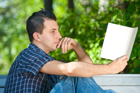 Handsome young man sitting on the bench and reading book outdoors Stock Photo - 10855423