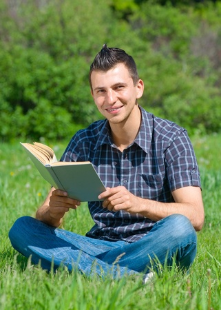 Handsome young man sitting on grass and reading book outdoors  photo