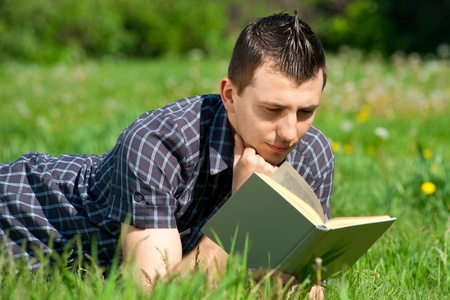 Handsome young man lying on grass and reading book outdoors  photo