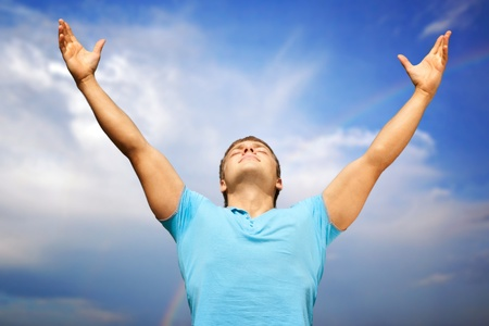 manos levantadas al cielo: Feliz el hombre joven con los brazos levantados y los ojos cerrados contra el cielo azul