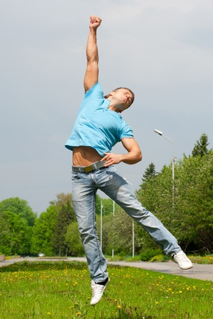 muscle guy: Happy young man jumping in air with arm extended