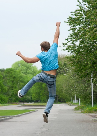 freedom park: Happy young man jumping in air with raised arms outdoors