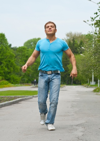 Handsome young man running through park photo