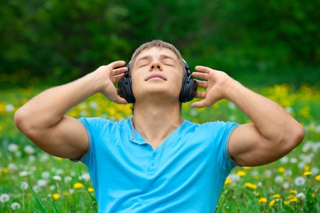 Portrait of a relaxed young man sitting on grass in park and listening to music on headphone  photo