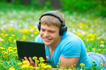 Happy young man working with a laptop and listening music on headphone outdoors photo