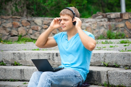 Young man working with a laptop and listening music on headphone outdoors photo