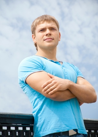 Portrait of handsome young man with crossed arms outdoors photo