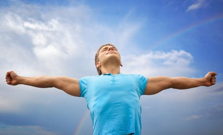 worship hands: Happy young man with raised arms and closed eyes against blue sky