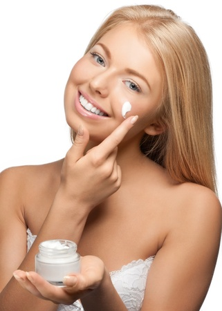 Portrait of young beautiful woman applying moisturizer cream on her face, isolated on white background photo