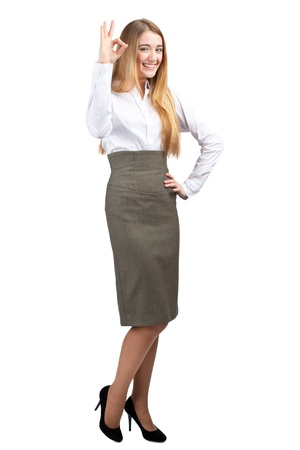 Full length portrait of confident young businesswoman showing OK sign and smiling, over white background photo