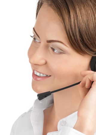 telephonist: Close-up portrait of a pretty young female call center employee wearing a headset, against white background