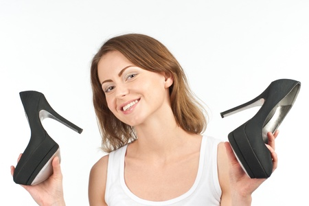 Portrait of pretty young woman holding a pair of black shoes and smiling, over white background  Stock Photo - 10856044
