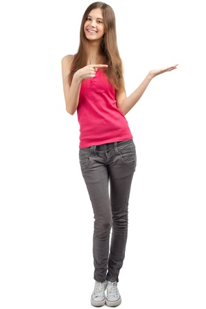 Full length portrait of beautiful casual girl pointing and showing something on the palm of her hand. Isolated on white background. photo