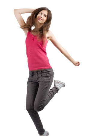 arm extended: Full length studio shot of happy young woman jumping and smiling. Over white background Stock Photo