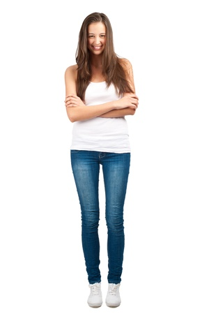 Full length portrait of a happy young woman standing with folded hand against white background photo