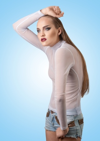 Fashion studio shot of young beautiful woman with long blond hair and bright professional make-up. Against blue background photo