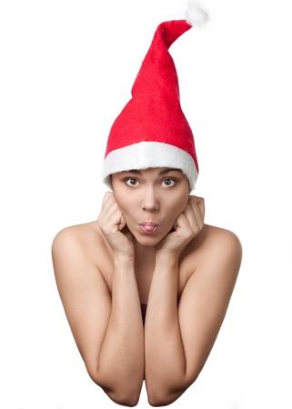 wearing santa hat: Funny portrait of pretty grimacing  woman wearing Santa hat against white background