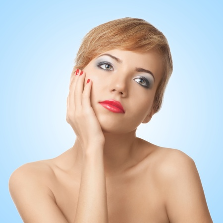 Portrait of  pretty young woman with red lipstick and manicure against blue background photo
