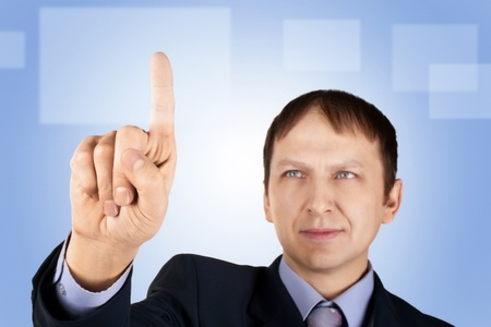 Portrait of a confident businessman pushing on imaginary button, over blue background photo