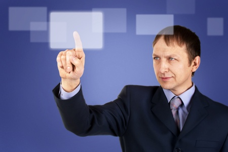 Portrait of a confident businessman pushing on touch screen, over blue background photo