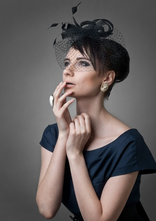 Studio portrait of a beautiful retro styled woman looking surprised and covering mouth with hand photo