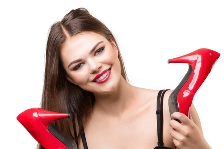 Portrait of pretty woman holding a pair of red shoes and smiling, over white background Stock Photo - 10947547