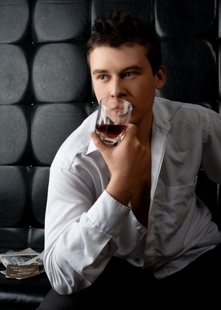 Handsome young man with glass of whiskey sitting on leather sofa and examining old photos photo