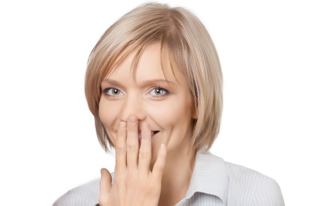 cara sorprendida: Retrato de mujer sorprendida bastante joven tapándose la boca con la mano y sonriente, sobre fondo blanco Foto de archivo