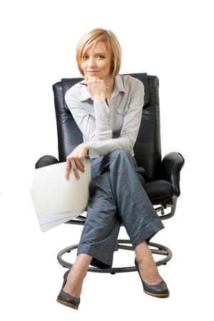 Attractive blond businesswoman sitting in the armchair and smiling, isolated on white photo