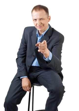 man front view: Handsome businessman sitting and pointing at viewer, isolated on white