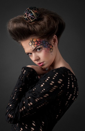 Expressive fashion studio shot of young and beautiful woman with professional art make-up and hairstyle photo