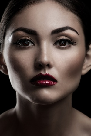 Fashion studio shot of beautiful young woman with make-up. Close-up portrait. photo