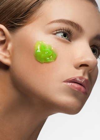 Close-up of young beautiful woman with green moisturizing facial mask on her face  photo