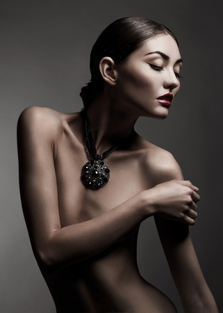 Fashion studio shot of beautiful naked woman with make-up and with a necklace around her neck photo