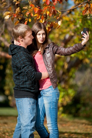 lover boy: Young beautiful couple walking in autumn park and taking pictures of themselves