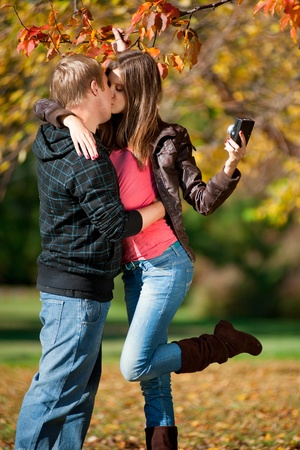 picture person: Young beautiful couple walking in autumn park and taking pictures of themselves