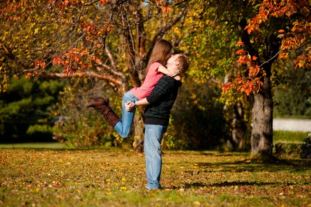 Young beautiful couple kissing in autumn park photo