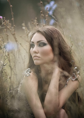 Portrait of young beautiful woman with bright makeup posing in field photo