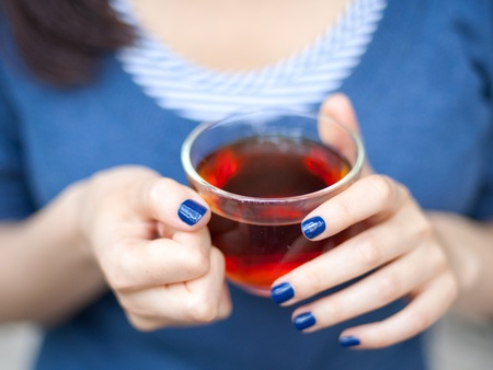 warm drink: Young lady holding a cup of tea (focus on fingers)