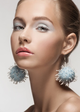 Close-up portrait of young beautiful woman with makeup and fancy earrings photo