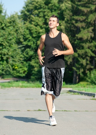 Young muscular man jogging in park photo
