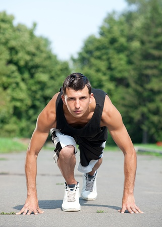 Young muscular man ready to start running in park photo