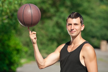 Young basketball player spinning basketball on finger  photo