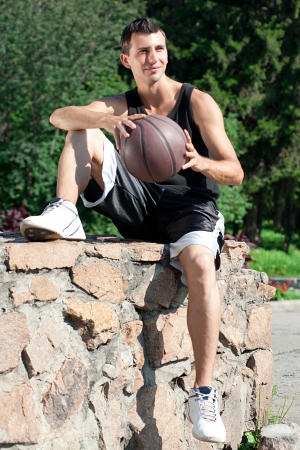 Young basketball player holding a ball in his hands and smiling photo