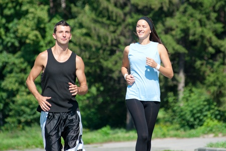 Young fitness couple of man and woman jogging in park photo