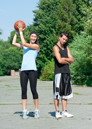 boy basketball: Young fitness couple of man and woman playing basketball outdoors Stock Photo